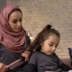 A Young Indian Mother Wearing a Hijab Combing Hair To Her Little Daughter While Child Reading a Book - VideoHive Item for Sale