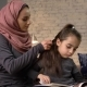 A Young Indian Mother Wearing a Hijab Makes a Hairstyle To Her Little Daughter While Child Reading a - VideoHive Item for Sale