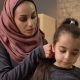 A Young Indian Mother Wearing a Hijab Makes a Hairstyle To Her Little Daughter and Talks, While - VideoHive Item for Sale