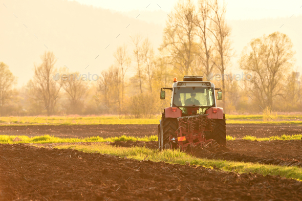 Farmer plowing soil at sunset in spring season - Stock Photo - Images