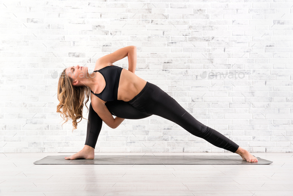 Fit woman doing utthita parsvakonasana yoga pose - Stock Photo - Images