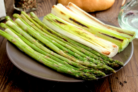leeks and green asparagus roasted on the grill in square tray, on classic wood - Stock Photo - Images