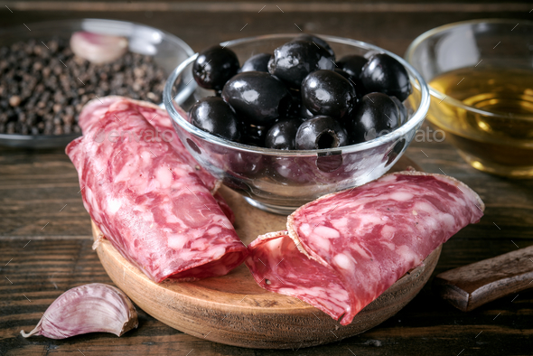slices of Iberian sausage and bowl of black olives on wooden board - Stock Photo - Images
