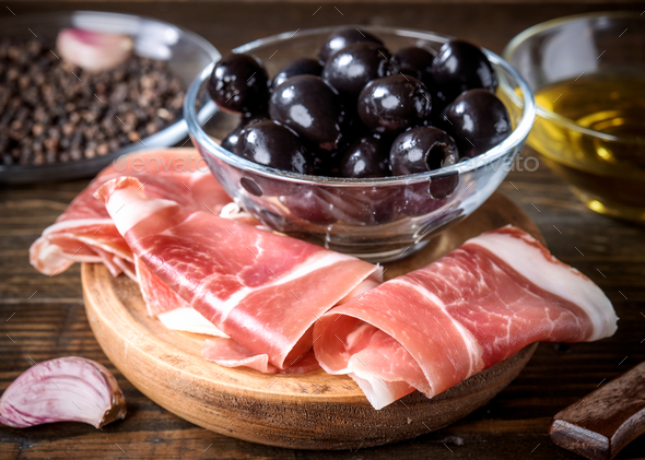 slices of Iberian ham and bowl of black olives on wooden board - Stock Photo - Images