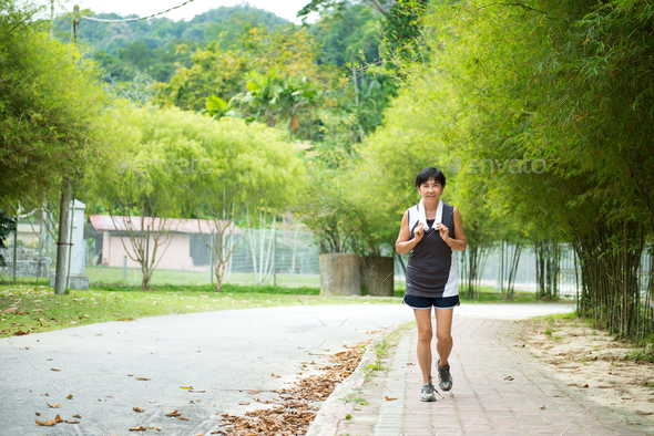 Front view of senior woman jogging through park - Stock Photo - Images