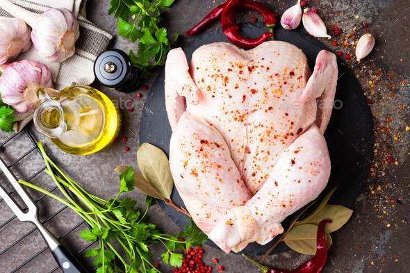 Raw chicken. Fresh whole chicken with ingredients for cooking - Stock Photo - Images