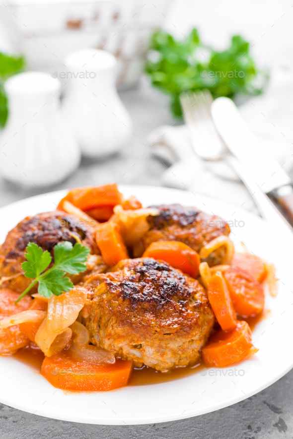 Fish meatballs or noisettes baked with carrot, onion and tomato sauce. Fish meatballs on plate - Stock Photo - Images
