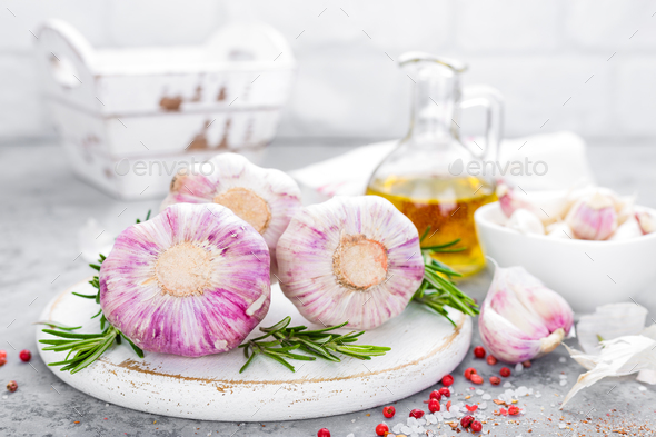 Garlic. Fresh garlic, oil and rosemary on kitchen table - Stock Photo - Images