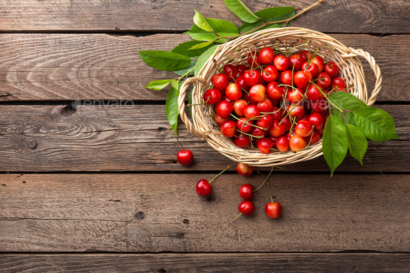 Cherry. Fresh sweet cherry with leaves in basket on wooden table - Stock Photo - Images