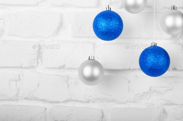 Christmas blue and silver balls on white brick wall holiday back - Stock Photo - Images