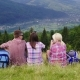 Friends of Tourists Sit in a Picturesque Place in the Background of the Mountains. They Rest, Admire - VideoHive Item for Sale