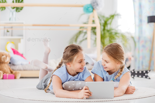 Twin girls sharing a tablet - Stock Photo - Images