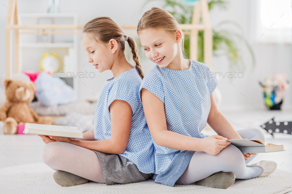 Twins sitting back to back - Stock Photo - Images