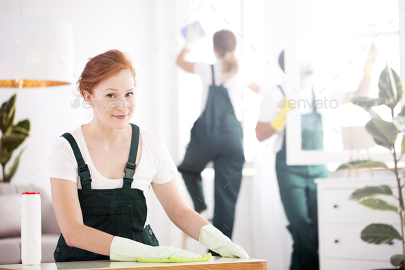 Cleaning lady dusting table - Stock Photo - Images