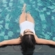 Fashion Woman in White Swimsuit Lying in Swimming Pool - VideoHive Item for Sale