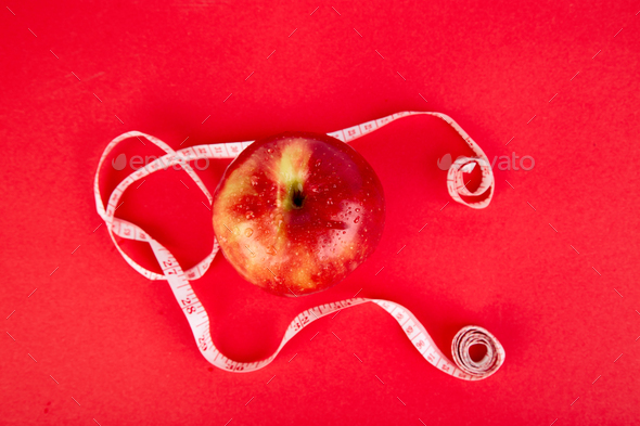 Measuring tape wrapped around a red apple - Stock Photo - Images
