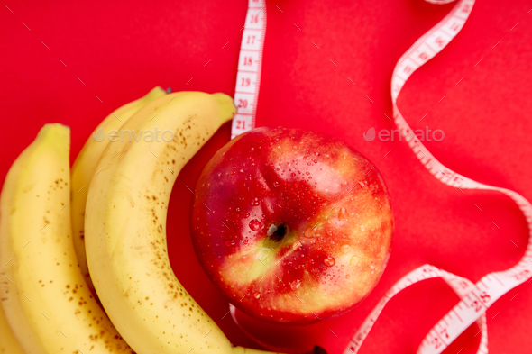 Measuring tape wrapped around a red apple and banana - Stock Photo - Images