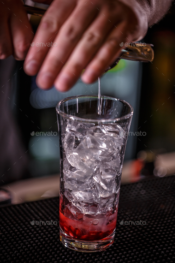 Barman hand squeezes lime juice - Stock Photo - Images