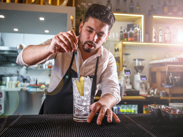 Bartender adding ginger into a glass - Stock Photo - Images