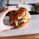 Huge burger on a wooden background close-up - PhotoDune Item for Sale