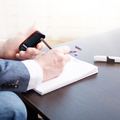 Man writing down measurement results from glucometer after blood - PhotoDune Item for Sale