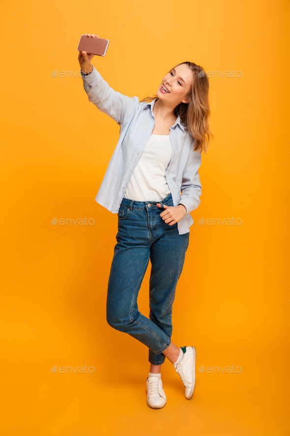 Studio portrait of beautiful woman smiling and taking selfie pho - Stock Photo - Images