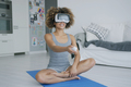 Cheerful sportswoman in VR glasses at home - PhotoDune Item for Sale
