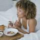 Dreaming woman having sweet meal in bed - PhotoDune Item for Sale