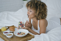 Dreaming woman having sweet meal in bed - PhotoDune Item for Sale