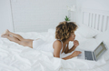 Pretty woman lounging on bed with laptop - PhotoDune Item for Sale