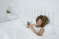 Smiling woman relaxing with phone in bed - PhotoDune Item for Sale