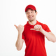 Image of handsome deliveryman in red uniform smiling and pointin - PhotoDune Item for Sale