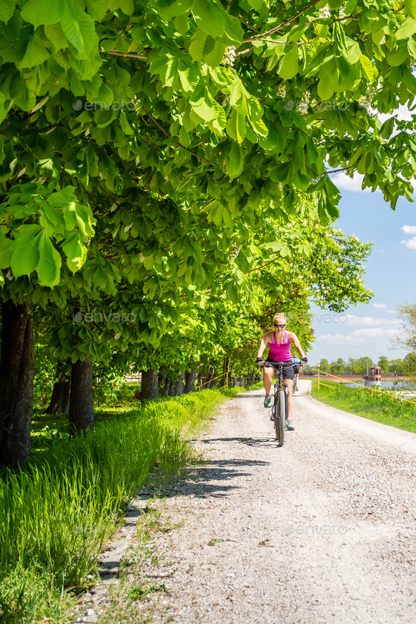 Woman cycling a mountain bike in city park, summer day - Stock Photo - Images