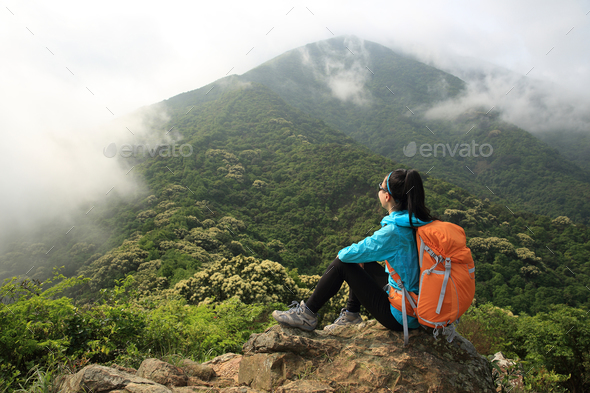 Hiker enjoy the view on spring forest mountain top  - Stock Photo - Images
