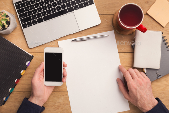 Man writing letter and holding smartphone - Stock Photo - Images