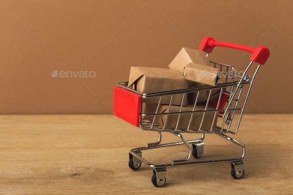 Miniature shopping cart and parcels on brown background, - Stock Photo - Images