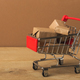 Miniature shopping cart and parcels on brown background, - PhotoDune Item for Sale