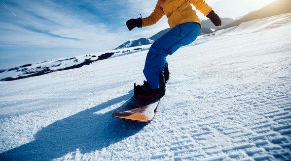 Snowboarding legs descent on winter mountain slope - Stock Photo - Images