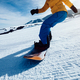 Snowboarding legs descent on winter mountain slope - PhotoDune Item for Sale