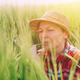 Female farmer examining wheat ears in field - PhotoDune Item for Sale
