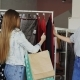 Free Download Girls Are Choosing Clothes While Standing Near Rails in Luxurious Shop. They Are Taking Skirt Nulled
