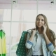 Free Download Young Woman Walking Through Clothing Department and Talking on Mobile Phone with Bags Nulled