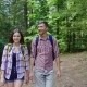 Young Couple of Tourists with Backpacks Walking in the Woods. Warm Summer Day - VideoHive Item for Sale
