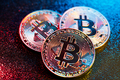 Three bitcoin coins in a colorful lighting. - PhotoDune Item for Sale