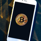 Phone with a bitcoin laying on top of it. - PhotoDune Item for Sale
