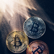 Three colorful bitcoin coins and beams of light. - PhotoDune Item for Sale