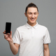 Cheerful young man standing isolated showing display of mobile phone. - PhotoDune Item for Sale