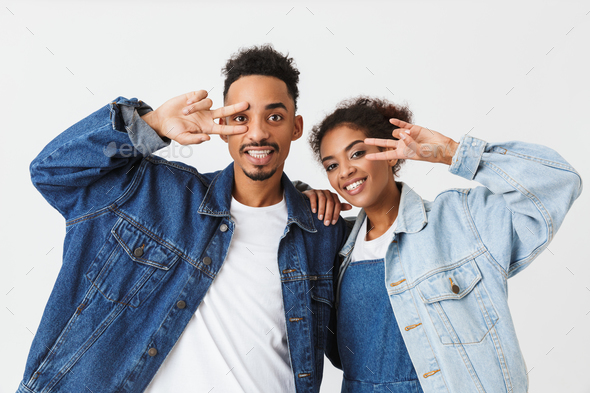 fde8db8278c Playful african couple in denim shirts showing peace gestures - Stock Photo  - Images