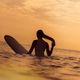 Surfer girl waiting in the line up for a wave at sunrise or sunset - PhotoDune Item for Sale