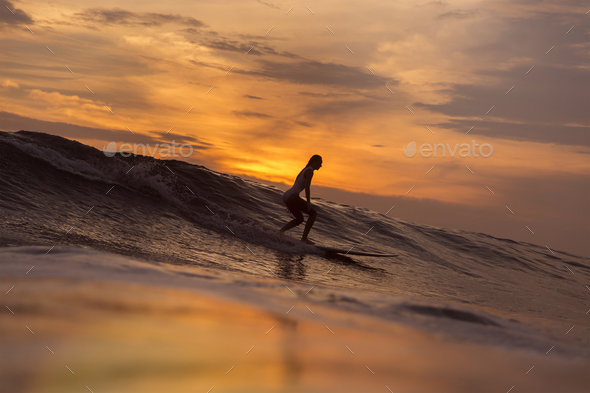 Surfer girl waiting in the line up for a wave at sunrise or sunset - Stock Photo - Images